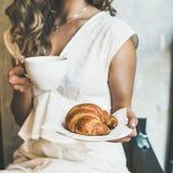 拿着新月形面包和热奶咖啡在咖啡馆,方形的庄稼的白肤金发的妇女 库存图片
