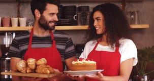 拿着新月形面包和蛋糕的盘子侍者和女服务员 影视素材