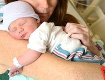 拿着新生儿的母亲在医院 免版税库存照片