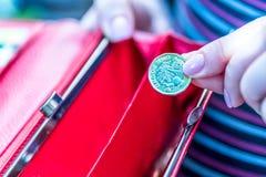拿着新的英国的女性手一个纯正的1英镑硬币钱包 库存图片