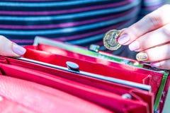 拿着新的英国的女性手一个纯正的1英镑硬币钱包 免版税库存照片