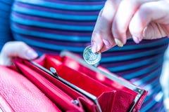 拿着新的英国的女性手一个纯正的1英镑硬币钱包 免版税库存图片