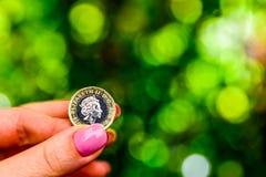 拿着新的英国的女性手一个纯正的1英镑硬币 免版税库存图片