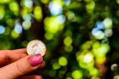 拿着新的英国的女性手一个纯正的1英镑硬币 库存图片