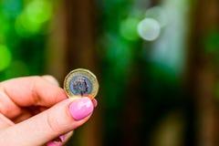 拿着新的英国的女性手一个纯正的1英镑硬币 库存照片