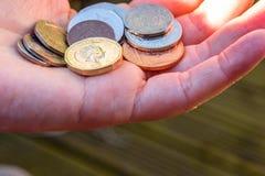拿着新的英国的女性手一个纯正的1英镑硬币 免版税库存照片