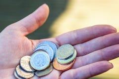 拿着新英国一个纯正的1英镑硬币的女性手 库存照片