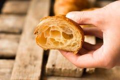 拿着新近地被烘烤的新月形面包的WomanÂ的手切成了两半,在可看见里面的酥饼 免版税库存照片