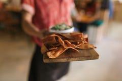 拿着新近地被烘烤的烤干酪辣味玉米片的服务板侍者 免版税库存照片