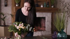 拿着新近地被装配的花花束的美丽的微笑的女性卖花人在演播室在桌然后投入 正 股票录像