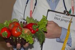 拿着新鲜水果和测量磁带的男性营养师,当站立时 库存图片