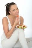 拿着新鲜的三文鱼沙拉的板材健康自然愉快的少妇 免版税库存照片