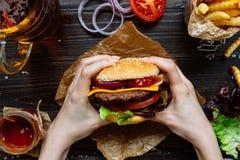 拿着新鲜的可口汉堡用炸薯条、调味汁和啤酒的手在木台式视图 免版税库存照片