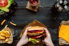 拿着新鲜的可口汉堡用炸薯条、调味汁和啤酒的手在木台式视图 免版税库存图片