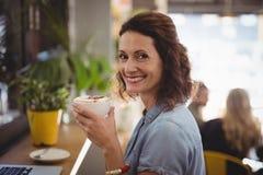 拿着新鲜的咖啡的微笑的妇女画象在咖啡馆 库存照片