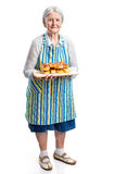 拿着新鲜的小圆面包的资深妇女 库存照片