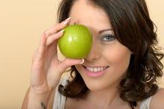 拿着新鲜的成熟水多的绿色苹果计算机的可爱的少妇 库存图片