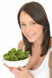 拿着新鲜的未加工的菠菜的板材愉快的可爱的少妇 免版税库存照片