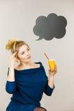 拿着新鲜的橙汁的妇女 免版税库存照片