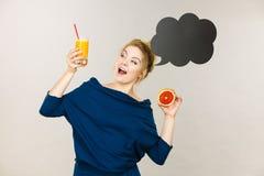 拿着新鲜的橙汁的愉快的妇女 库存图片