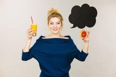 拿着新鲜的橙汁的愉快的妇女 免版税库存照片