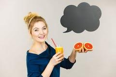 拿着新鲜的橙汁的愉快的妇女 免版税图库摄影