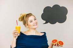 拿着新鲜的橙汁的愉快的妇女 图库摄影