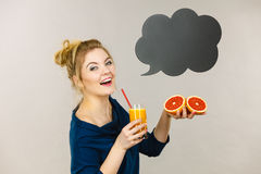 拿着新鲜的橙汁的愉快的妇女 库存照片