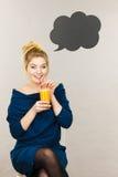 拿着新鲜的橙汁的愉快的妇女 免版税库存图片