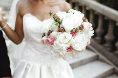 拿着新鲜的玫瑰的美丽的新娘婚姻花束 免版税图库摄影