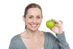 拿着新鲜的绿色苹果的健康自觉妇女 图库摄影