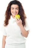拿着新鲜的绿色苹果的端庄的妇女 免版税库存照片