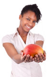 拿着新鲜的芒果的年轻愉快的黑人/非裔美国人的妇女 免版税库存照片