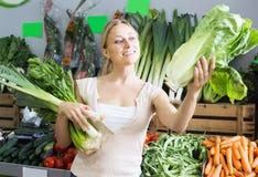 拿着新鲜的芹菜和韭葱的可爱的年轻女性顾客 免版税库存照片