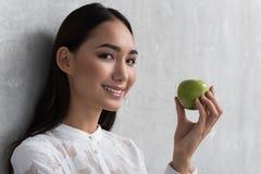 拿着新鲜的苹果的喜悦的女孩手中 图库摄影