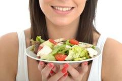 拿着新鲜的鸡丁沙拉的板材可爱的愉快的健康少妇 库存照片