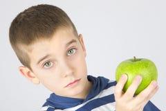拿着新鲜的绿色苹果的年轻男孩 免版税库存图片