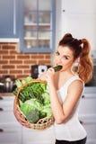 拿着新鲜蔬菜和叮咬黄瓜的篮子运动的穿戴的美丽的白种人女孩 免版税库存图片