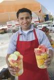 拿着新鲜水果沙拉的男性摊贩 图库摄影