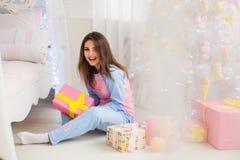 拿着新年礼物的微笑的女孩 免版税图库摄影