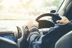拿着方向盘的汽车司机手 免版税库存图片