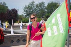 拿着旗子的快乐的妇女 免版税库存照片