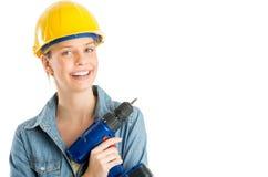拿着无绳的钻子的愉快的女性建筑工人 免版税库存图片