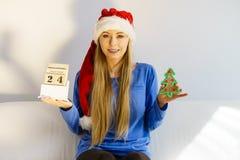 拿着日历和树的圣诞节妇女 图库摄影