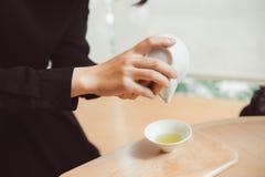 拿着日本人在泥罐的手Sencha茶 免版税库存照片