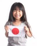 拿着日本旗子的逗人喜爱的矮小的亚裔女孩画象  免版税库存照片