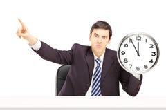 拿着时钟和打手势与他的手指的恼怒的商人 免版税库存照片