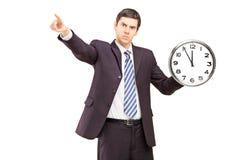拿着时钟和指向与手指的恼怒的商人 库存照片