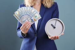 拿着时钟和金钱在颜色背景的女实业家 时间安排 免版税库存图片