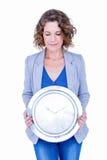 拿着时钟的一名急切女实业家 免版税库存图片
